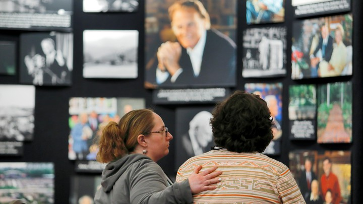A mourner is comforted near a display of pictures of Billy Graham in Asheville, North Carolina, in 2018.