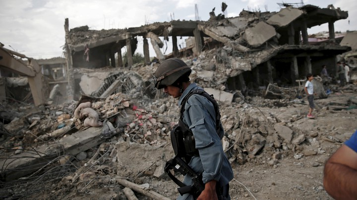 An Afghan policeman walks past a ruined building and a pile of rubble.