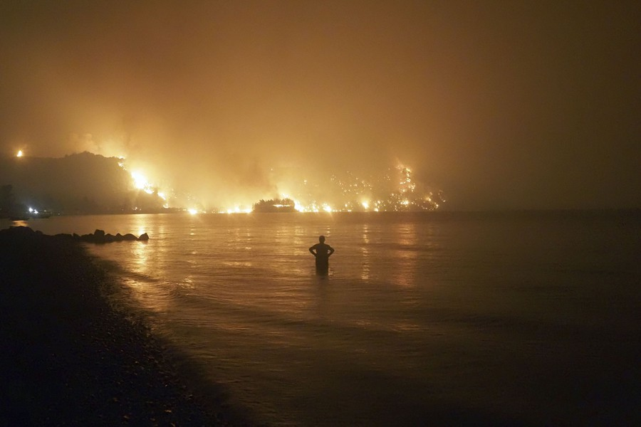 A man standing knee-deep in the water watches as a wildfire approaches the shoreline at night.