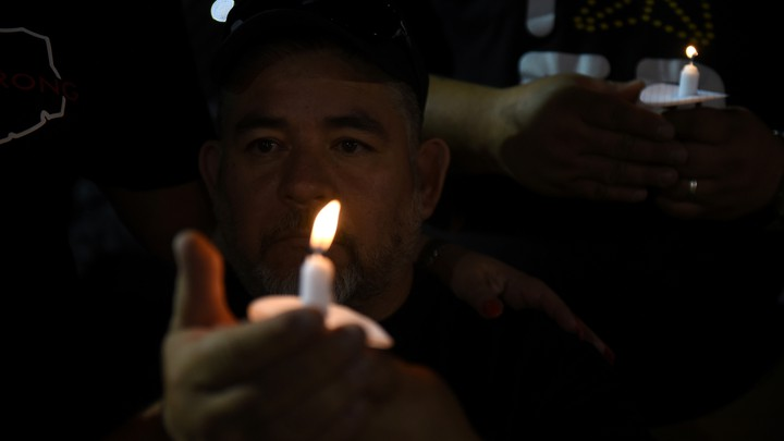 Man holding a candle at vigil after mass shooting in El Paso