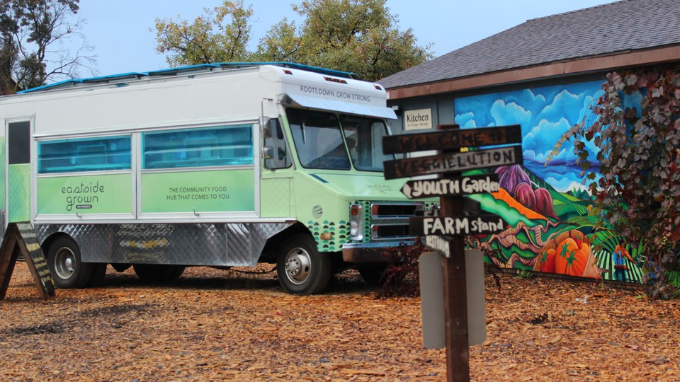 A green and blue food truck parked outside a colorful building