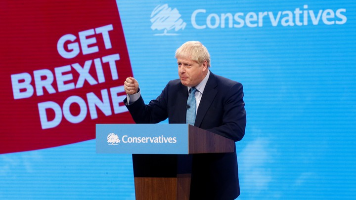 Boris Johnson speaks in front of a lectern with a banner for his Conservative Party behind him.