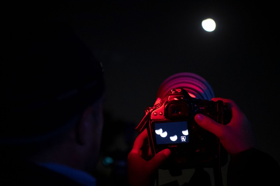 A photographer aims a camera at the moon.