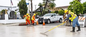 Workers apply a reflective coating to a street in a Southern California neighborhood.