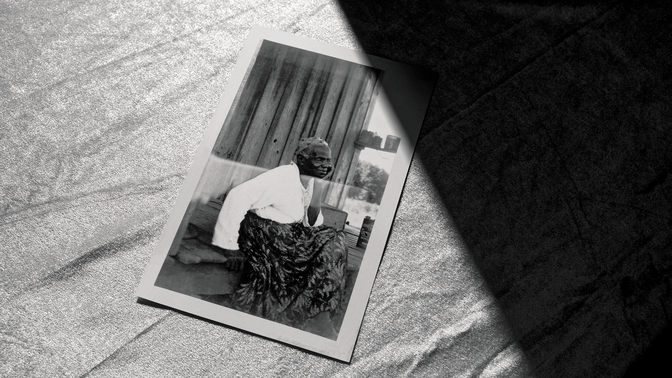 photo from the Federal Writers Project archive of a woman sitting outside a wooden house