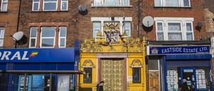 An ornately decorated yellow doorway with gold doors stands out on a row of brick buildings with commercial shopfronts.