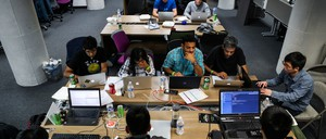 Tech workers sit around a table on their laptops in San Francisco, California