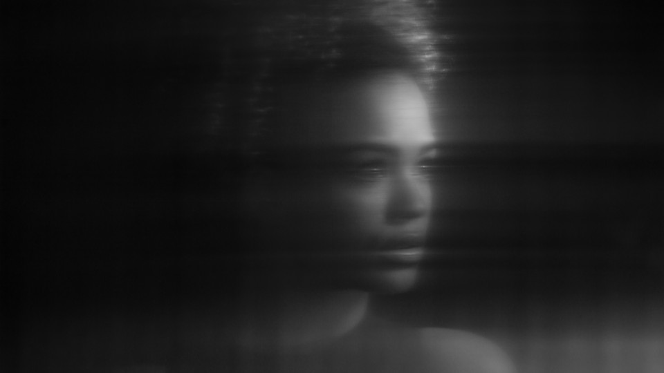A blurry black-and-white image of a young woman