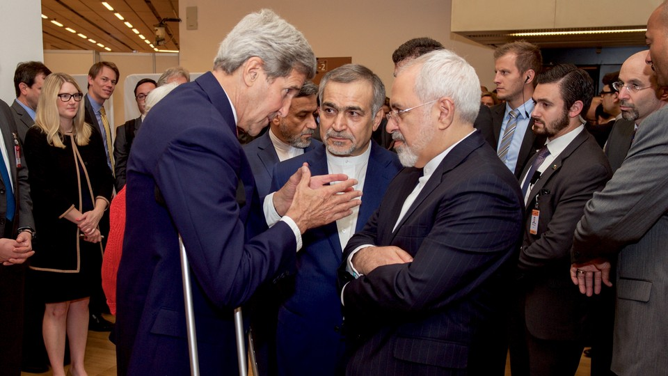 U.S. Secretary of State John Kerry speaks with Hossein Fereydoun, the brother of Iranian President Hassan Rouhani, and Iranian Foreign Minister Javad Zarif before addressing an international press corps on the nuclear deal on July 14, 2015.