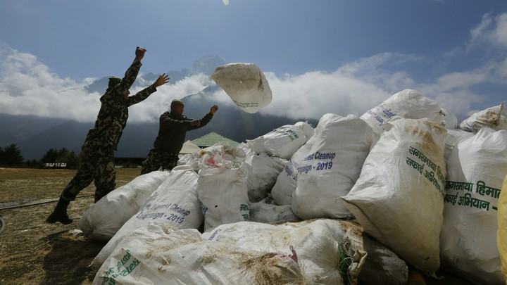 Nepalese men pile up garbage collected from Mount Everest on May 27, 2019