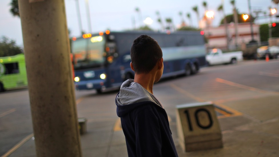 A migrant waits for a bus to Atlanta after being released from a detention center in McAllen, Texas on May 9, 2017.