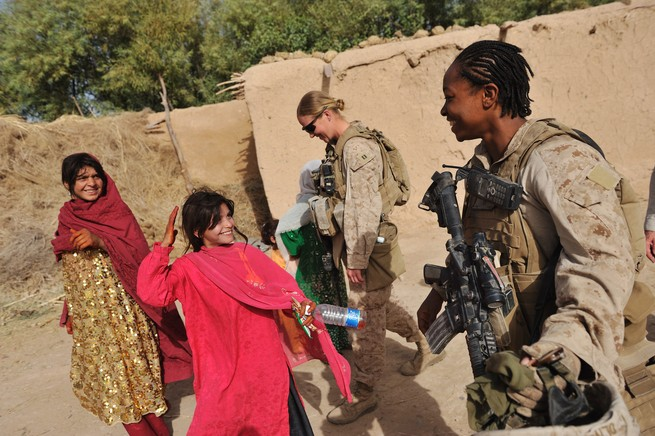 A US soldier laughs with Afghani girls