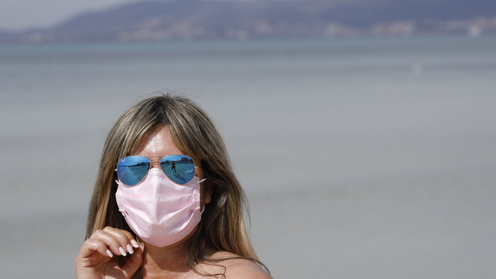 A woman on a beach in blue reflective sunglasses and a pink face mask