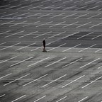 A skateboarder in an empty parking lot