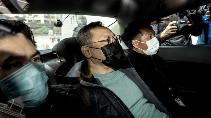 Three men sit in the backseat of a car with masks on as photographers stand outside.