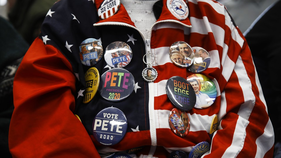 A Pete Buttigieg supporter, seen from the neck down, wears an American-flag jacket covered in pro-Buttigieg buttons.