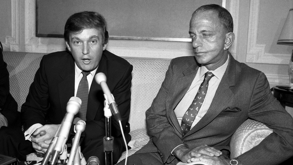 A black and white photo of Donald Trump sitting in front of microphones next to Roy Cohn.