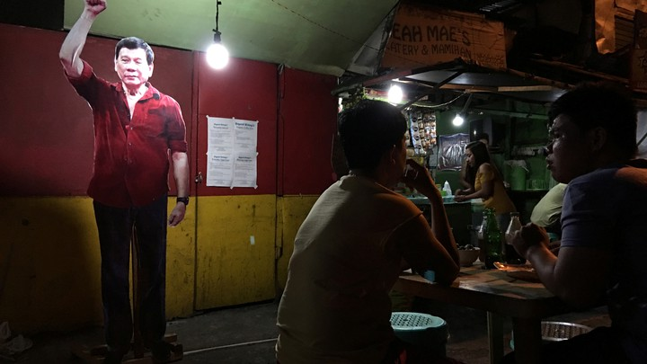 A life-size cut-out of President-elect Rodrigo Duterte looms over diners at a street stall in the center.
