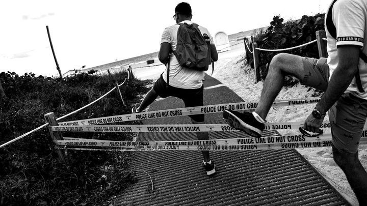Two boys crossing police tape to gain entrance to a beach.