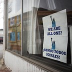 "A person walks past a storefront with a sign in the window reading ""We Are All One"""