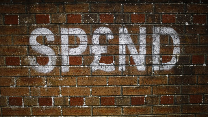 "Graffiti on a brick wall in the U.K. spells out ""SPEND."""