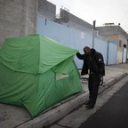 An LAPD officer looks in a tent on Skid Row in Los Angeles, California.