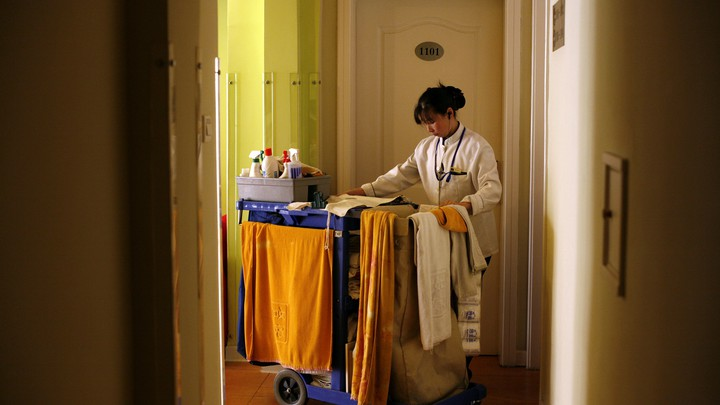 A hotel maid enters a room with a cart of cleaning supplies.