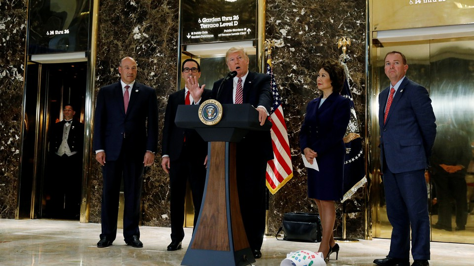 Donald Trump speaks at a podium in the lobby of the Trump Tower.