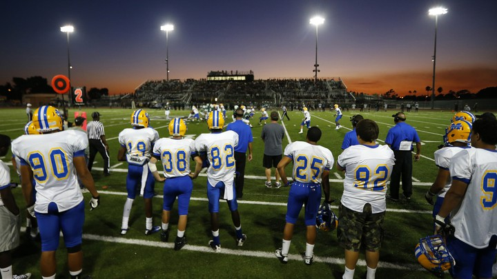 High-school football players look out onto the field as a game is played under the lights.