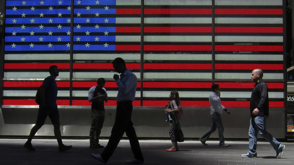 Pedestrians walk past an American flag in part of Times Square in New York City.