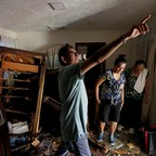 Three people inspect flood damage to an apartment.