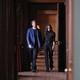 Prince Harry and Meghan Markle walk down a hallway.