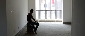 A man sits in a room alone.