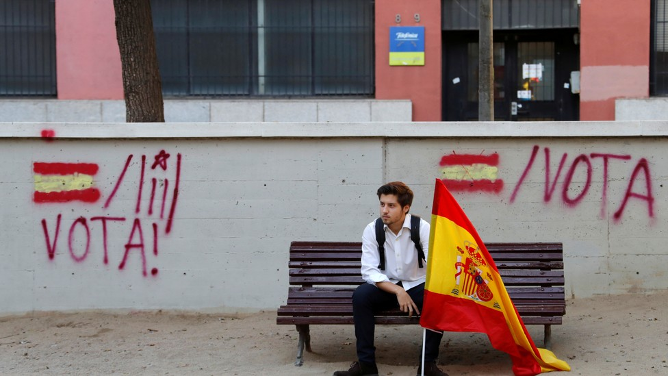 A man holding a Spanish flag sits on a bench before a pro-union demonstration organized by the Catalan Civil Society in Barcelona, Spain on October 8, 2017.