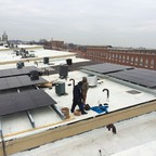 Solar panel installers work on the rooftops of some of Baltimore's poorest neighborhoods.