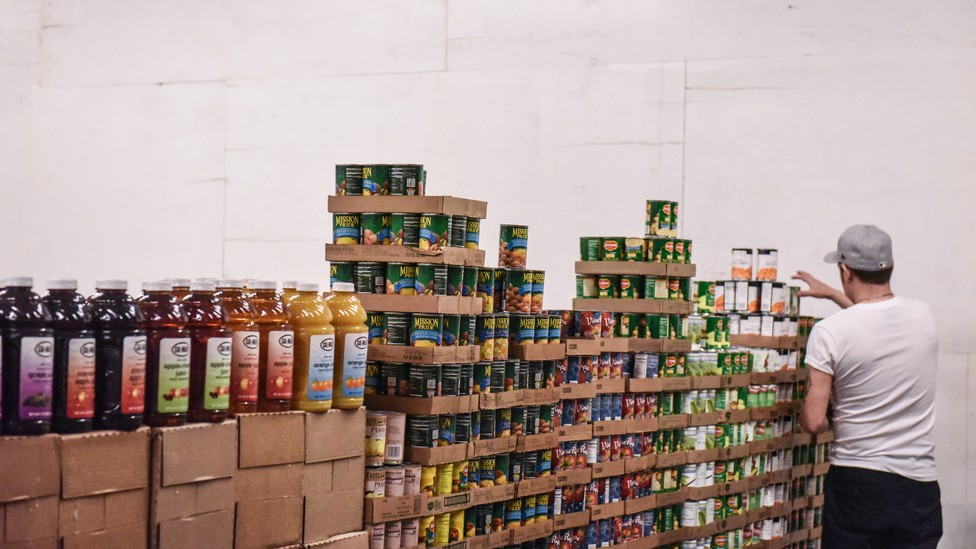 A worker stacks canned food inside a food distribution center