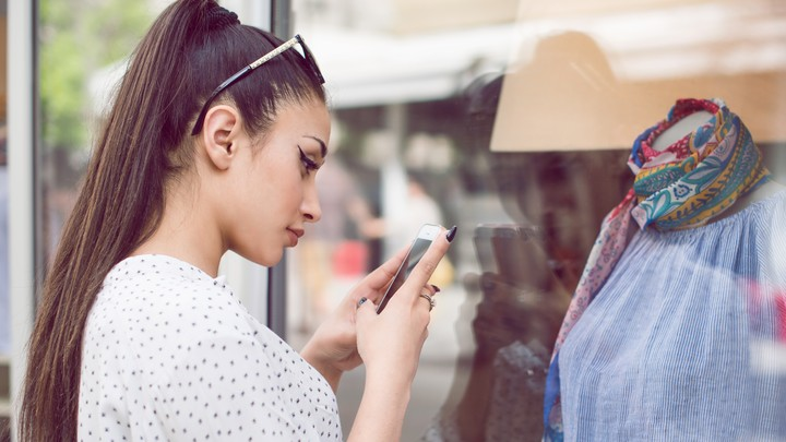 A woman uses a smartphone to take a picture of clothing on a mannequin.
