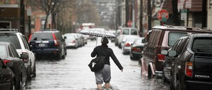A person holding an umbrella walks down a flooded street in Hoboken, New Jersey.