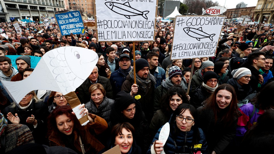People with signs shaped like sardines gather in Italy.