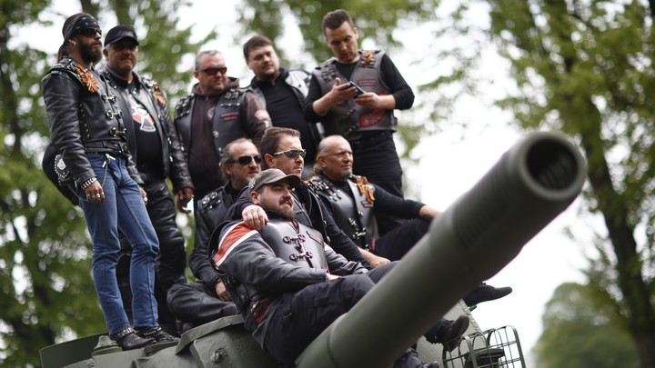 Members of the Night Wolves motorcycle group pose on top of a Red Army tank.