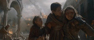 Still from 'Game of Thrones' showing three characters trudging through a burning city.