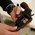 A police officer displays a handgun checked in during a community gun buy-back program.