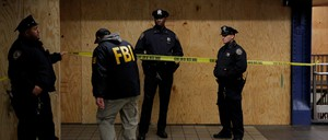 Law-enforcement officers stand at a New York City crime scene.