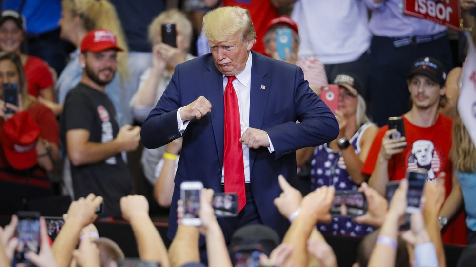 President Donald Trump gestures to the crowd before exiting a campaign rally.