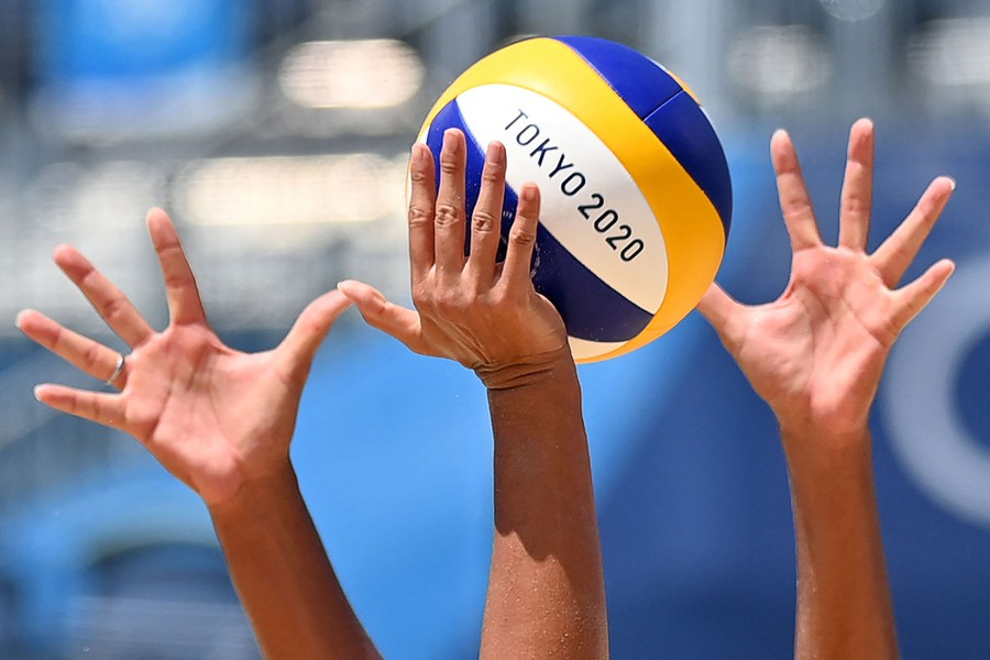 Several hands reach up for a volleyball.