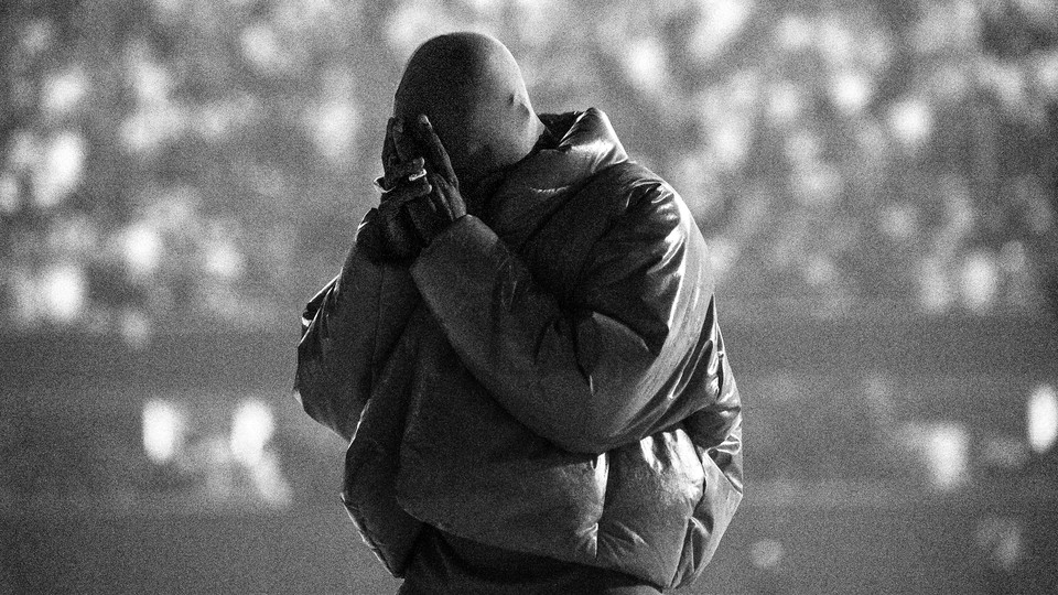 A black-and-white image of Kanye West, with his head bowed and his hands over his face, at a 'Donda' listening event last month