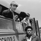 Black and white West Charlotte High School students pose together in and around their school bus in 1972.