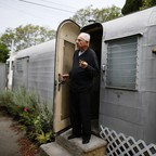 An elderly man stands in the doorway of his mobile home.