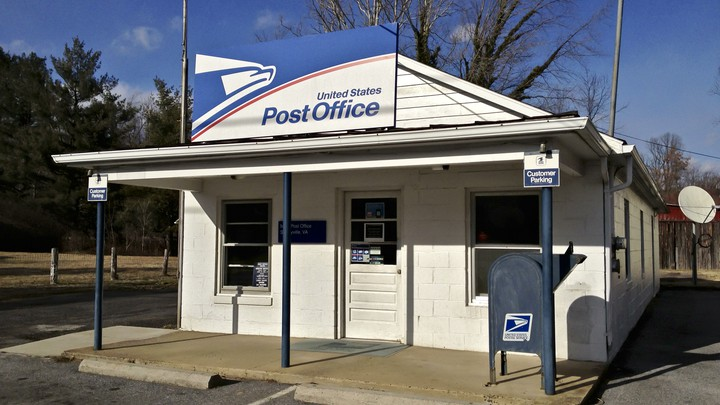 A white building with a United States Post Office sign on a clear day
