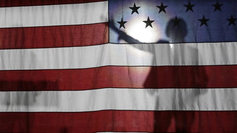 Senator Elizabeth Warren is seen in silhouette giving a speech to a crowd in Queens, New York.